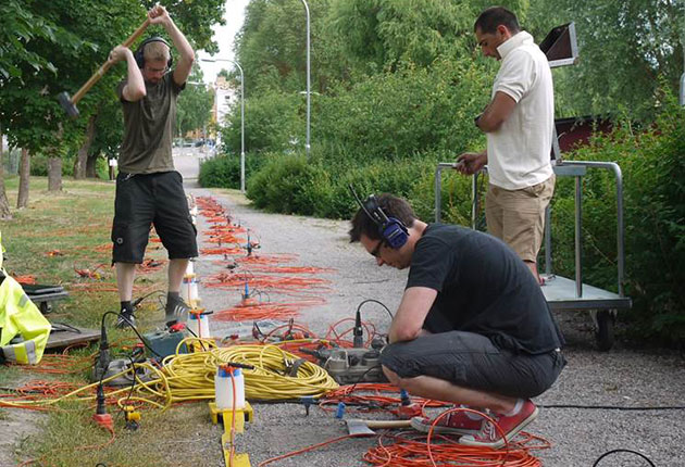 Three people and a variety of cables and seismic equipment. Photo.