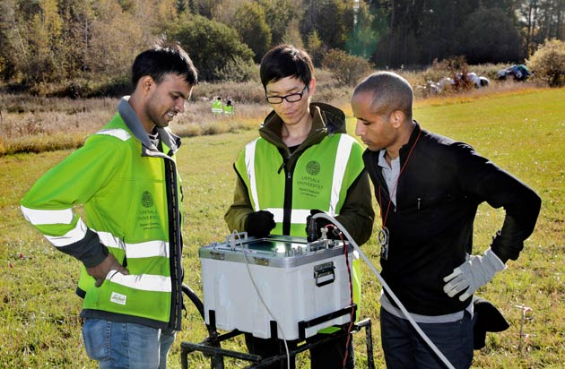 Three people with measuring equipment. Photo.