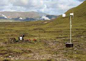 Seismic measuring equipment on a field in the mountains. Photo.