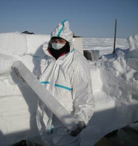 A person in a snowy landscape is holding a cylindrical piece of ice. Photo.
