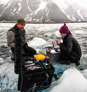 Two people with measuring equipment on ice. Photo.