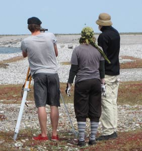 Three people with meteorological measuring equipment in a field. Photo.