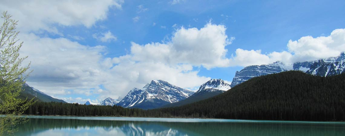 A lake with snow-capped mountains in the background. Photo.